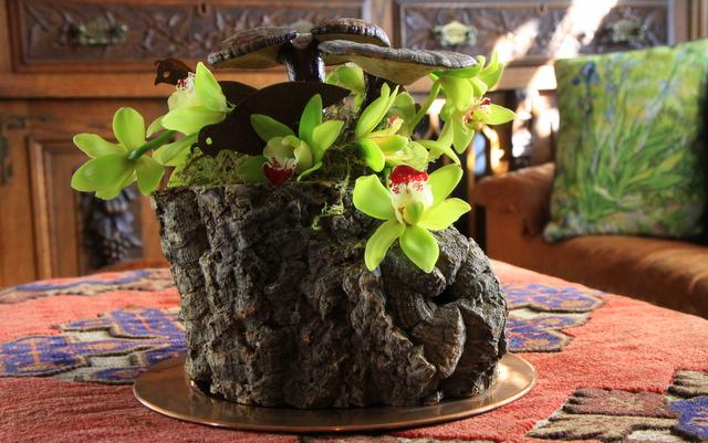 orchid arrangment with rusty garden art