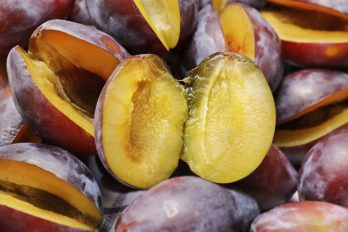 Picture of plums, some cut in half